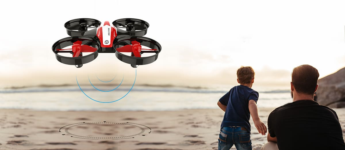 A family of three on the beach, including parents and a boy. A quadcopter is in the sky