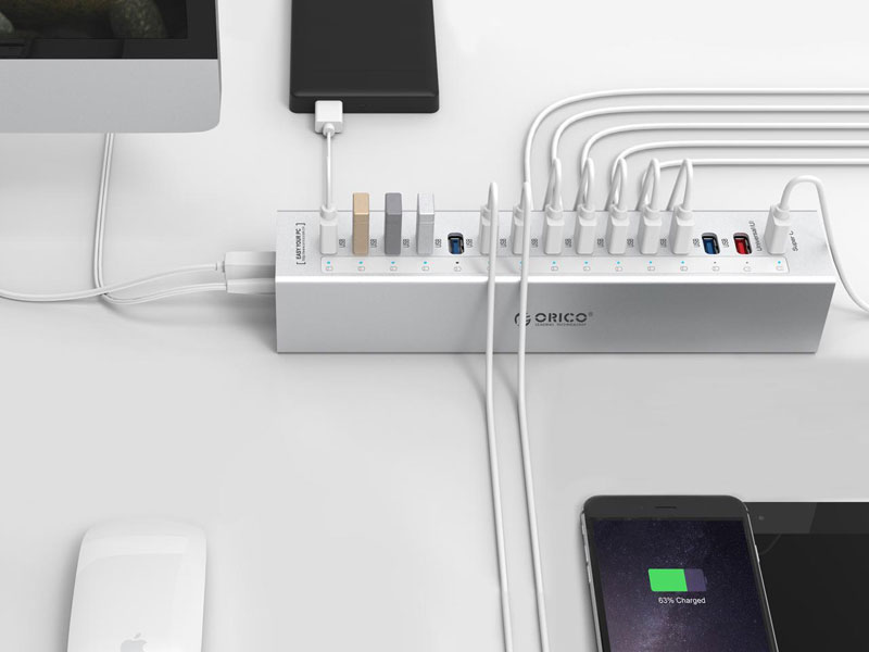 The Orico Hub On a white surface with all but three ports being used next to an apple mouse, imac, smartphone, tablet and external battery