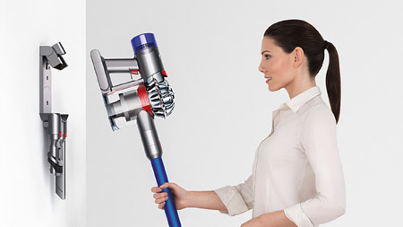 a woman placing Dyson V7 Fluffy to its docking station