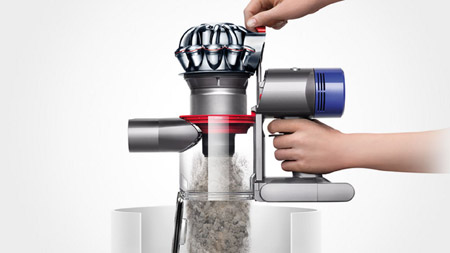 a hand is push the button to empty the bin of Dyson V7 Fluffy