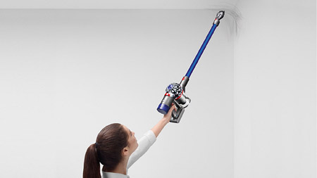 a woman lifting Dyson V7 Fluffy to cleaning the ceiling