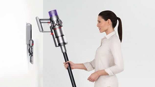 a woman putting Dyson Cyclone V10 to the docking station