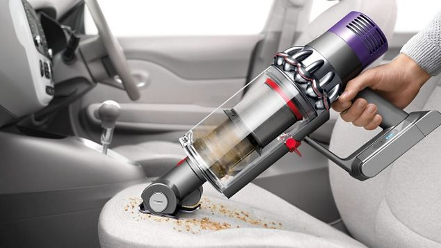 handheld vacuum cleaner cleaning debris on car seat