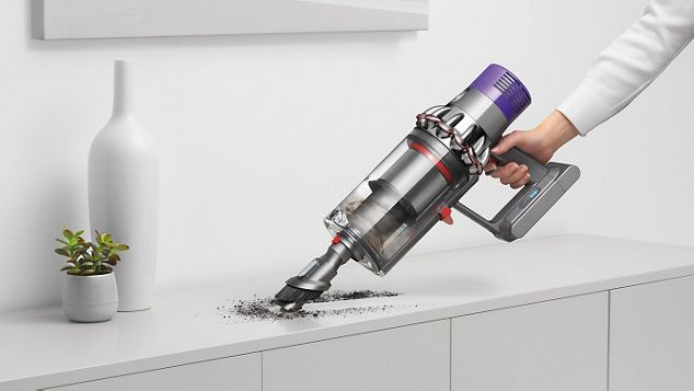 a hand holding Dyson V10 cleaning kitchen shelf