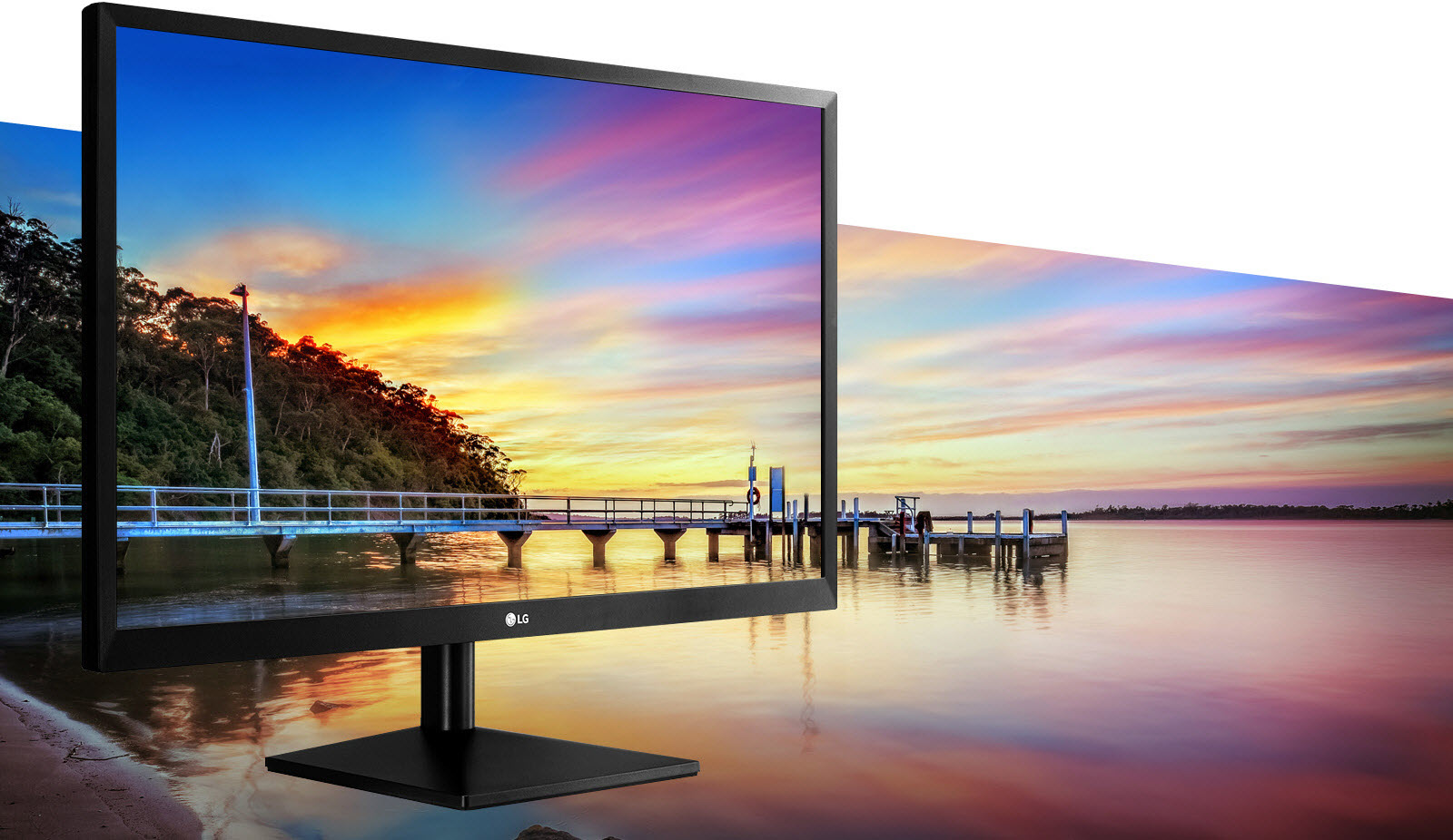 LG Monitor Angled to the Right Blending with the Background Image of a Dock by Water and Trees at a Colorful Twilight hour