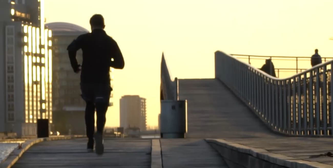 A man running on a sidewalk city trail during the morning