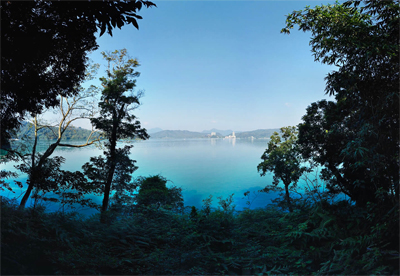 A morning day image of a light blue body of water in between forest trees
