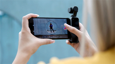 Osmo Pocket connected to a phone in a woman's hands as she prepares to capture