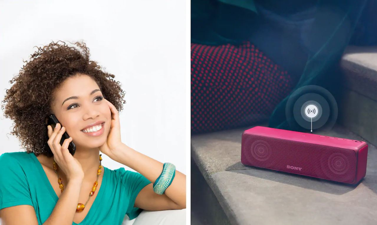 A girl is listening to a call while the speaker is playing music