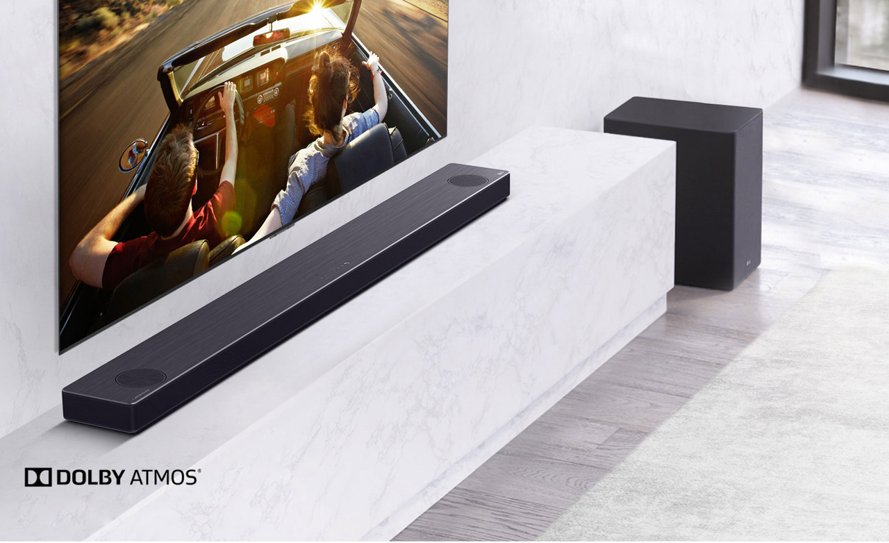 A sound bar and a subwoofer is beneath a TV.