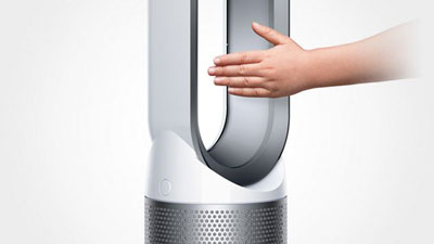 A man puts his hand in the air outlet of the purifier fan