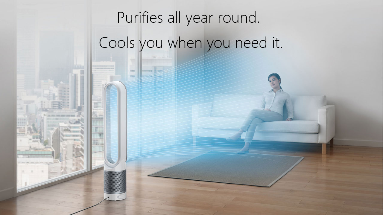A Dyson TP02 Pure Cool Link tower purifier fan delivering cooling, purified air to a female sitting in a couch in a living room, with texts at top center reading as