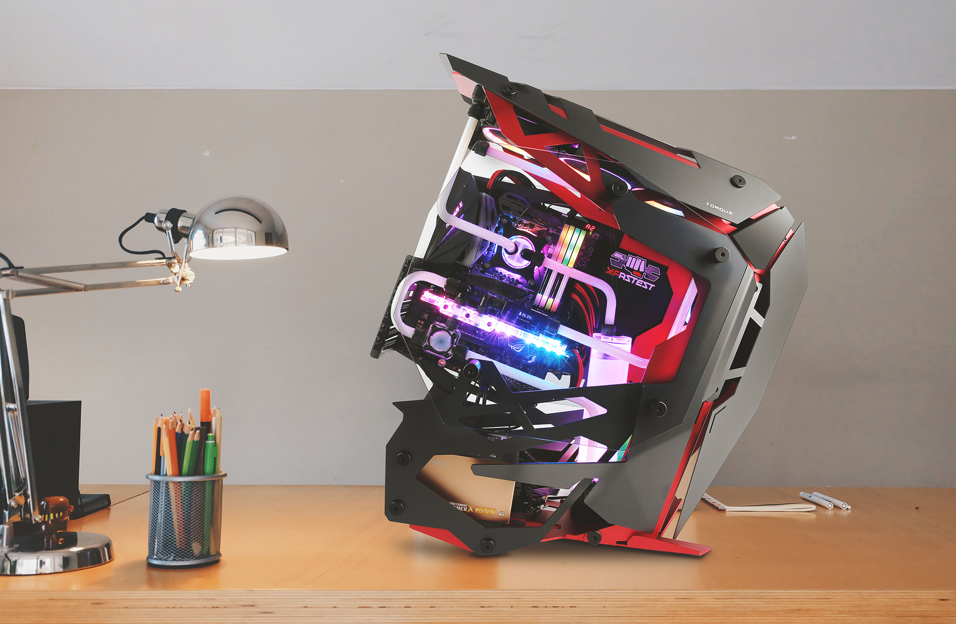 Antec TORQUE on a desk with a container of pencils and a desk lamp.