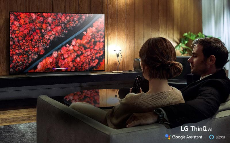 a man and a woman sitting on the sofa are watching LG E9 Glass Smart OLED TV