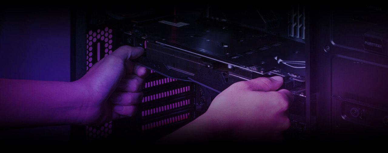 A graphics card held horizontally by two hands, in front of a motherboard in a computer case