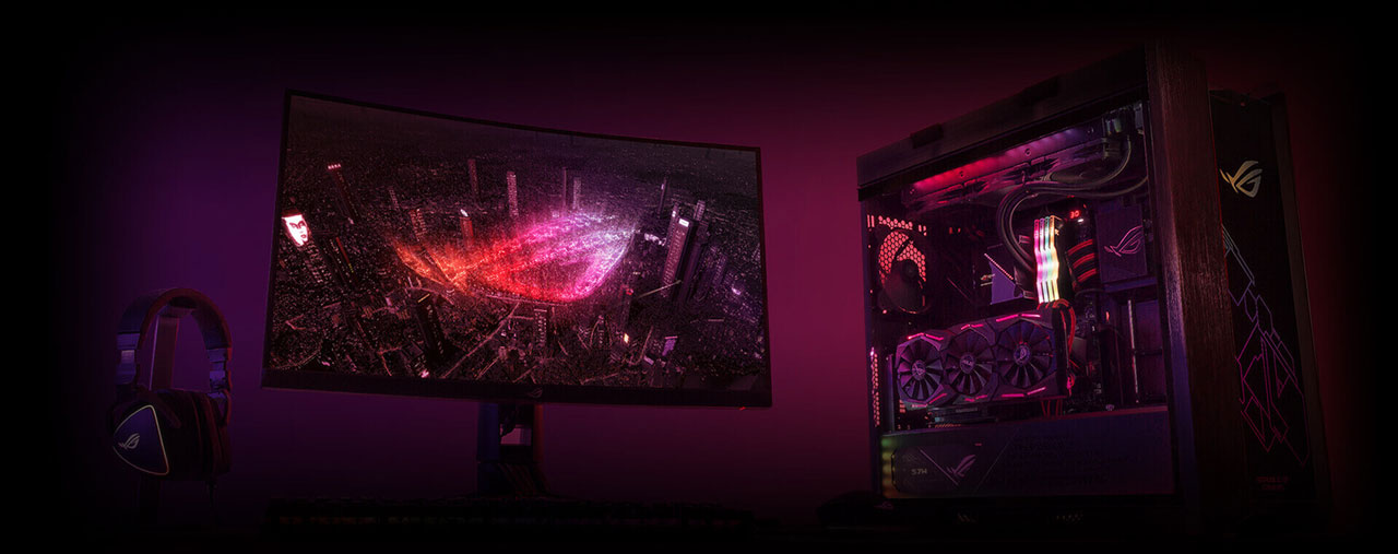 A gaming rig on display, including a monitor, an RGB illuminated desktop, and an ROG headset