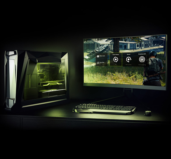 A PC, monitor keyboard + mouse setup showing lighting from the desktop PC and a game screenshot on the monitor