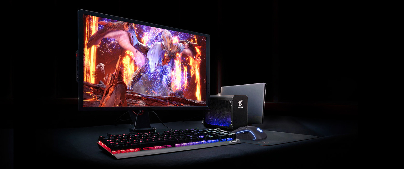 A gaming setup with the external graphics card connected to a laptop, a monitor showing a dragon in fiery domain and a keyboard + mouse