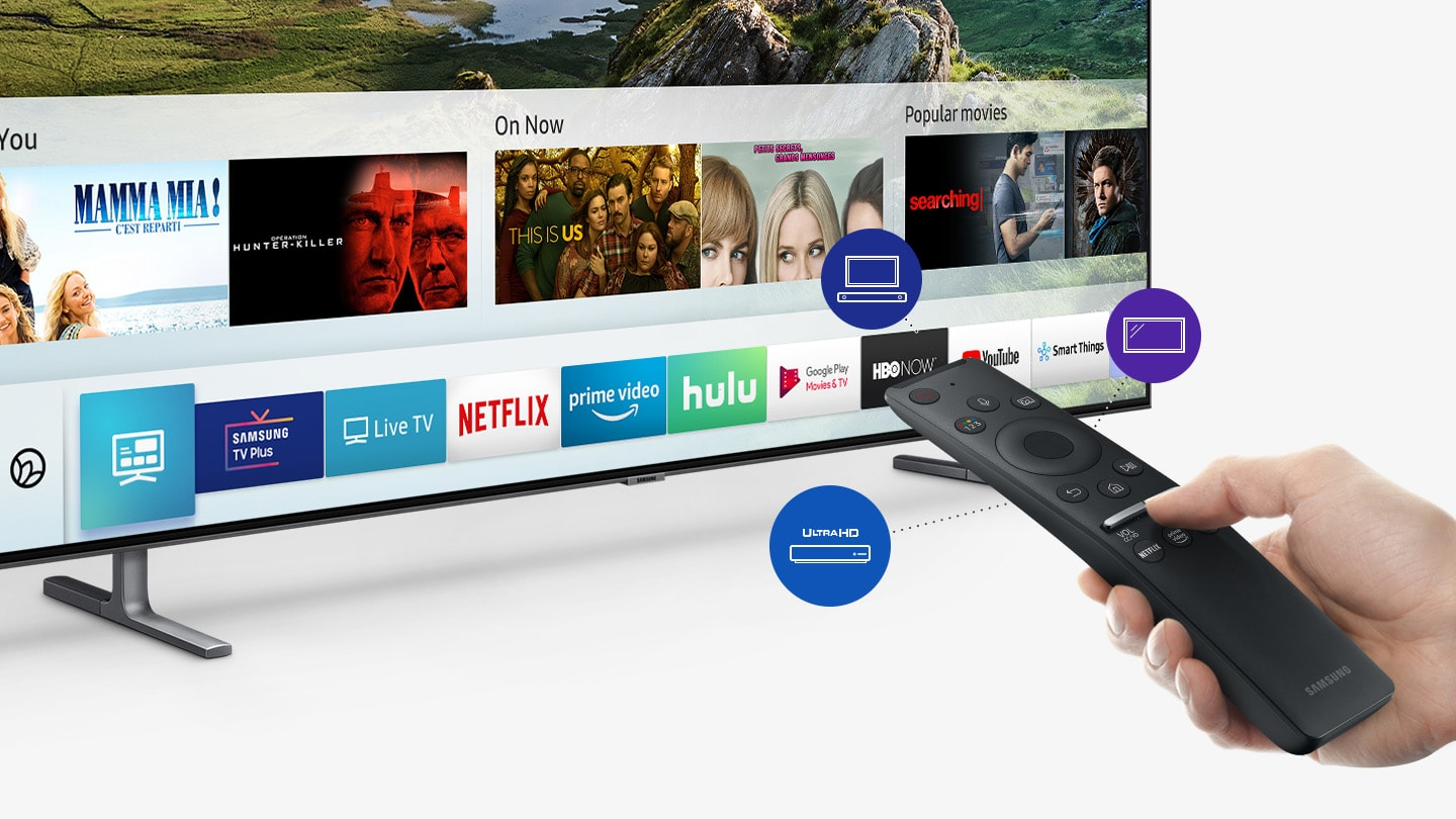 Hand holding a remote pointed towards a SAMSUNG Q80R angled down to the right, showing Title cards and app cards for shows and streaming services