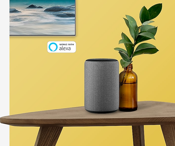 Corner of the SAMSUNG Q80R mounted on a yellow wall, on a wooden table with amazon alexa next to a bottle-potted plant
