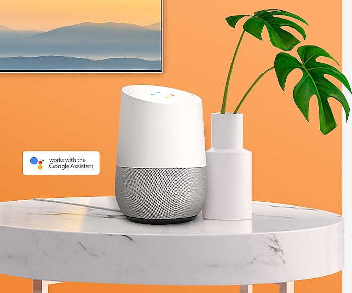 SAMSUNG Q80R mounted on an orange wall, with the google assistant on a marble table next to a potted plant
