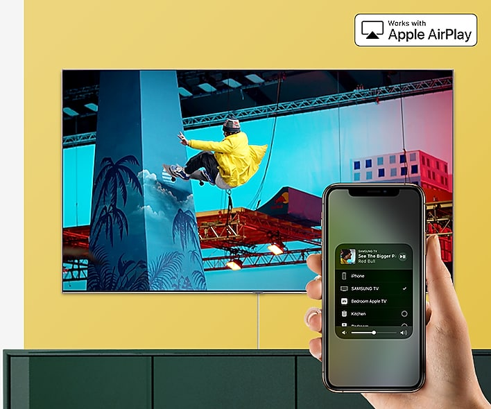 SAMSUNG Q80R Mounted on a Yellow Wall above a Green Cabinet. At the forefront is a hand holding a smartphone with AirPlay 2 up