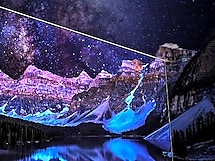 Paint splashes in front of a star-lit mountain range with tinges of purple, pink and black