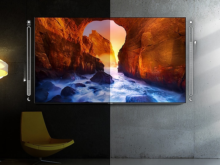 SAMSUNG Q80R TV Mounted on a Wall, Split in the Middle with a Brightness and Darkness Slider, It is darker on the left side of the image. The TV screenfill shows a river running through a canyon at sunset