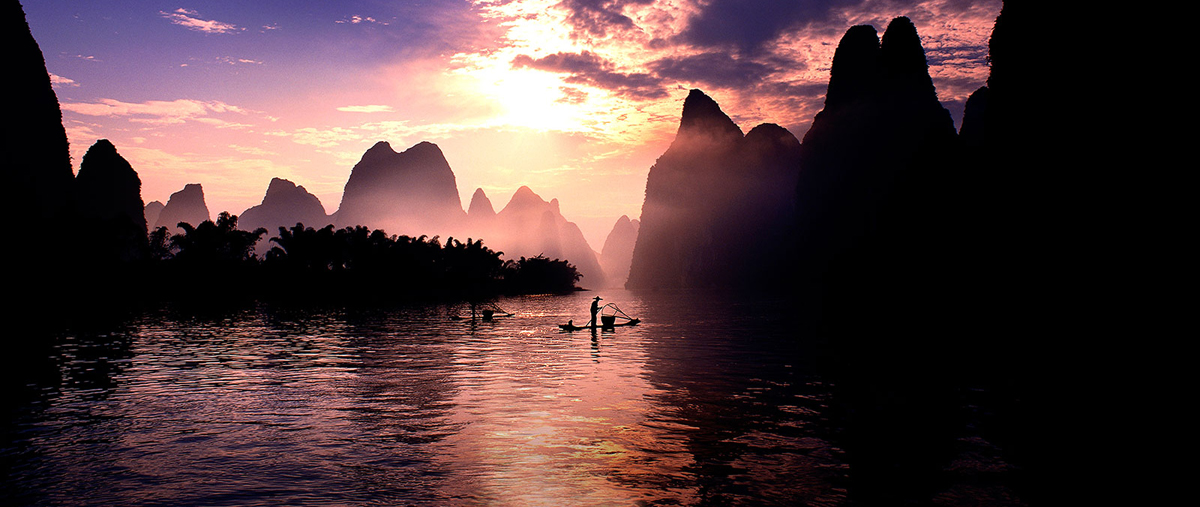 A scenery with two fishers on their own boats individually on a river surrounded by mountain ranges is in silhouette