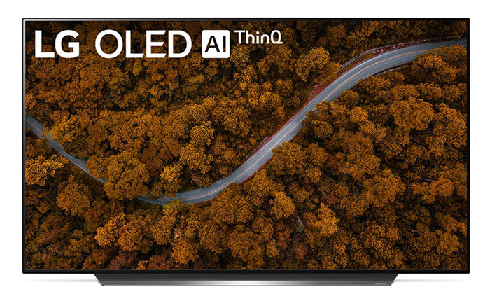 A TV is displaying a road cuting across a forest with orange trees. In the top left corner is text reading LG OLED AI ThinQ
