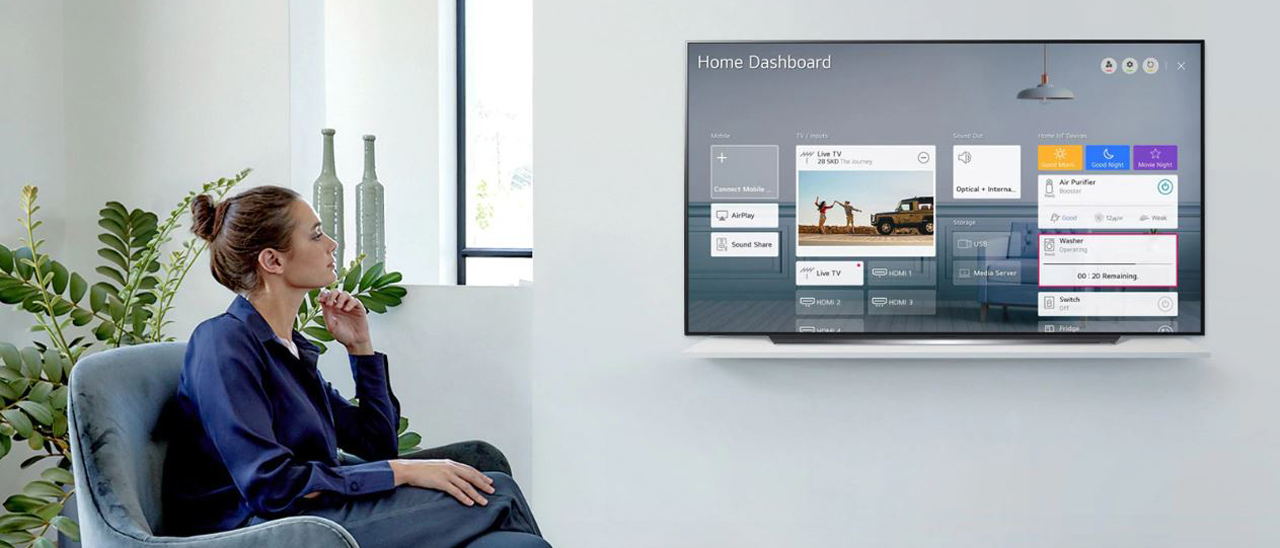 A woman is watching a TV with the home dashboard on display.
