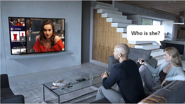 A woman is asking who the woman on the TV is.