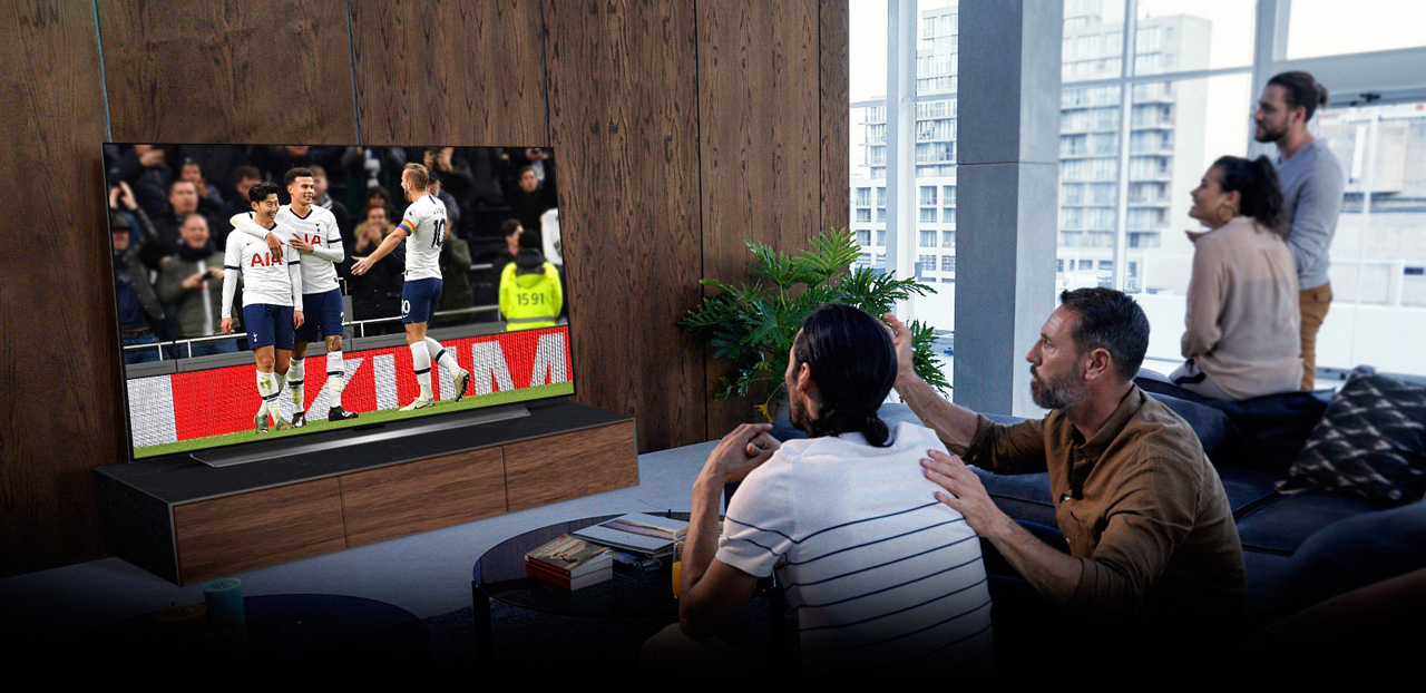 Four people are watching a football match on TV