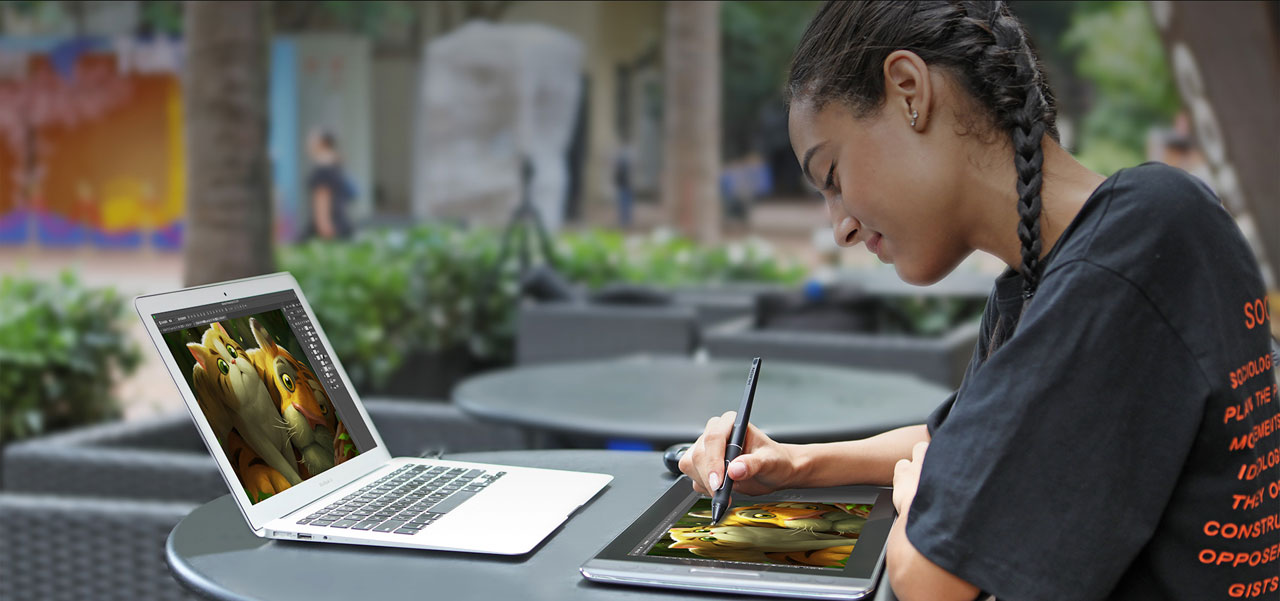 A female drawing on the Huion KAMVAS PRO 13 pen display, in front of a MacBook Air