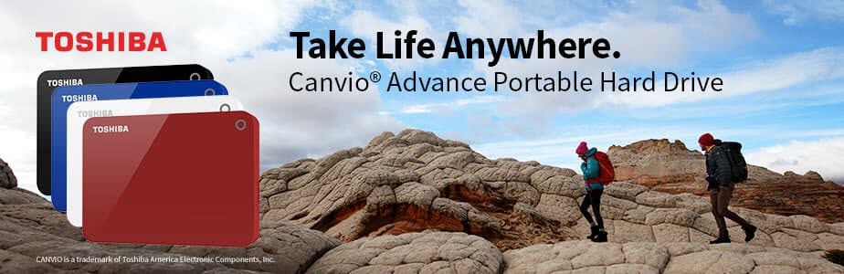 Toshiba Canvio Advance banner showing the four colors of the product: black, blue, white and red in front of a man and woman hiking through mountainous terrain and overhead text that reads: Take Life Anywhere.