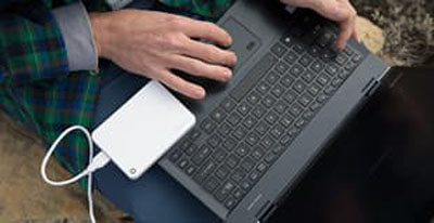 a white toshiba canvio advance plugged into a laptop that is being used by someone in their lap outdoors