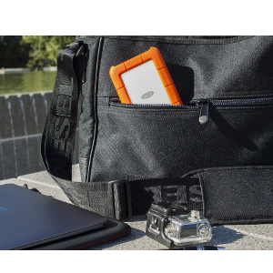 LaCie STFR1000800 sticking out of a black messenger bag on the floor outdoors, next to an ipad in a case and a cased go-pro camera