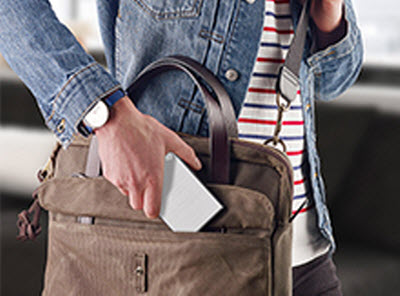 a person is puting Backup Plus Portable into his bag