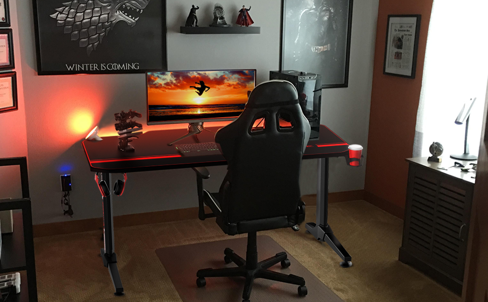 The Vitesse 55-inch gaming desk in front of a wall in a room, with the charging stack, a gaming monitor and a desktop on it. On the wall are mounted two paintings, and mini figures including Superman and Batman. In front of the desk is a racing style gaming chair