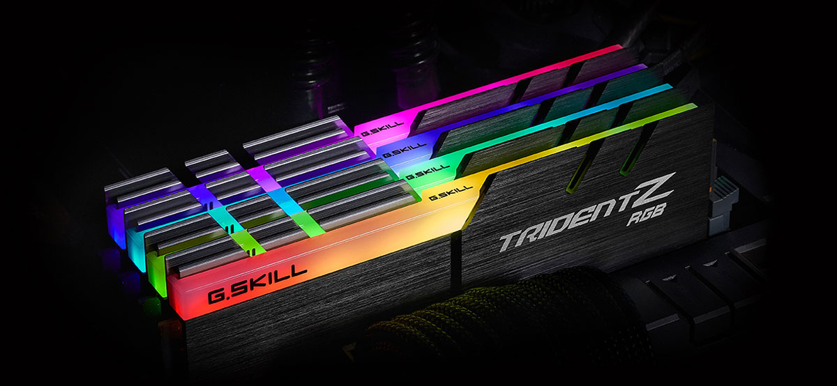 Top front view of four Trident Z modules on a motherboard, each glowing different colors on the RGB strip
