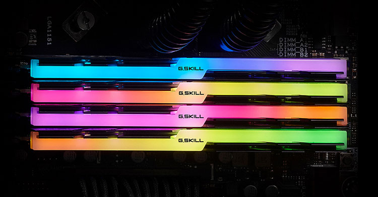 Top view of four Trident Z modules on a motherboard, with each module glowing different colors on the RGB strip