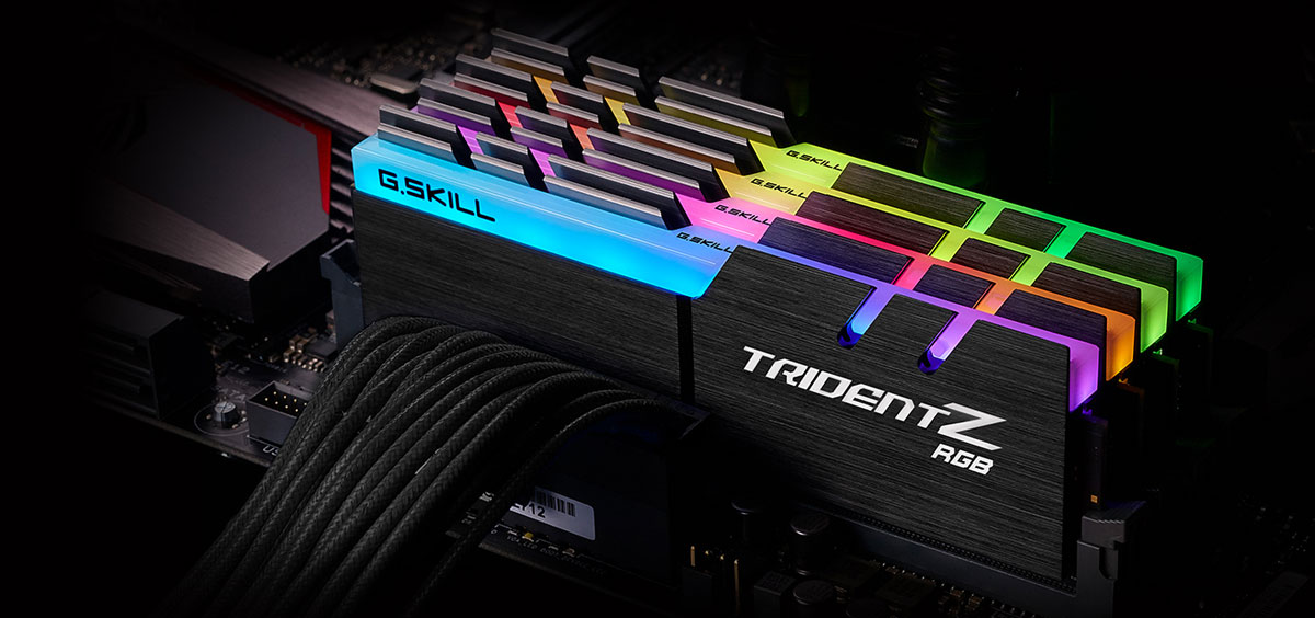 Top front view of four Trident Z modules on a motherboard, all facing slightly to the left, with each module glowing different colors on the RGB strip