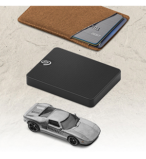 Black Expansion SSD top view, a wallet and a model car
