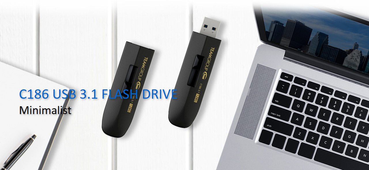 Team Group C186 Flash Drives Next to an Open Macbook Laptop and a pen with notebook. One flash drive is closed and the other is open. There is text that reads: C186 USB 3.1 FLASH DRIVE - Minimalist