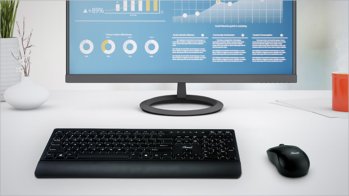 The Rosewill RKM-1000 keyboard and mouse on a white desk in front a computer monitor that has graphics of usage statistics