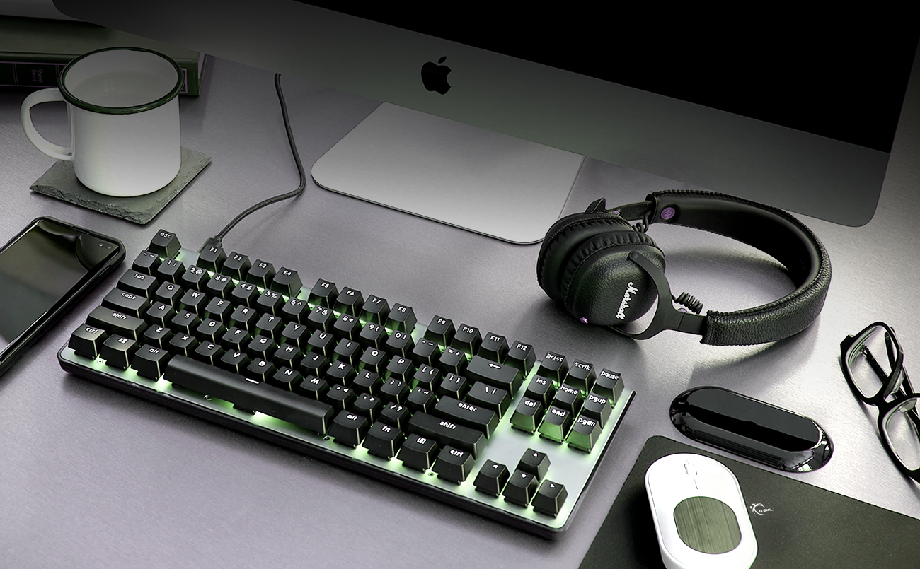 a black keyboard with a backlighting, a headphone, a mouse, a glasses, a cup of water, a phone and a computer