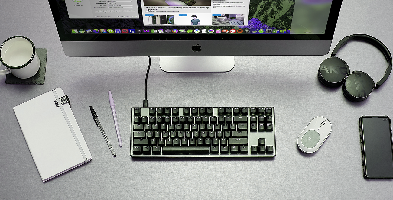 a desktop with a computer, a black keyboard, a mouse, a phone , a cup of water, a notebook, a headphone and two ballpens