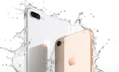 Rear view of upper part of iPhone 8 and iPhone 8 Plus, surrounded by splashes of water