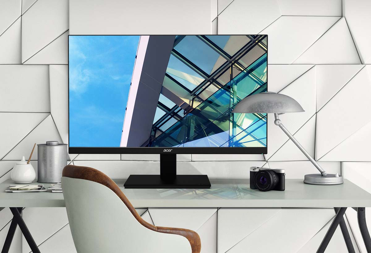 Acer V277U on a desk next to a DSLR camera, lamp, modernly stylized wall and a screenfill of the edge of windows on a modern building