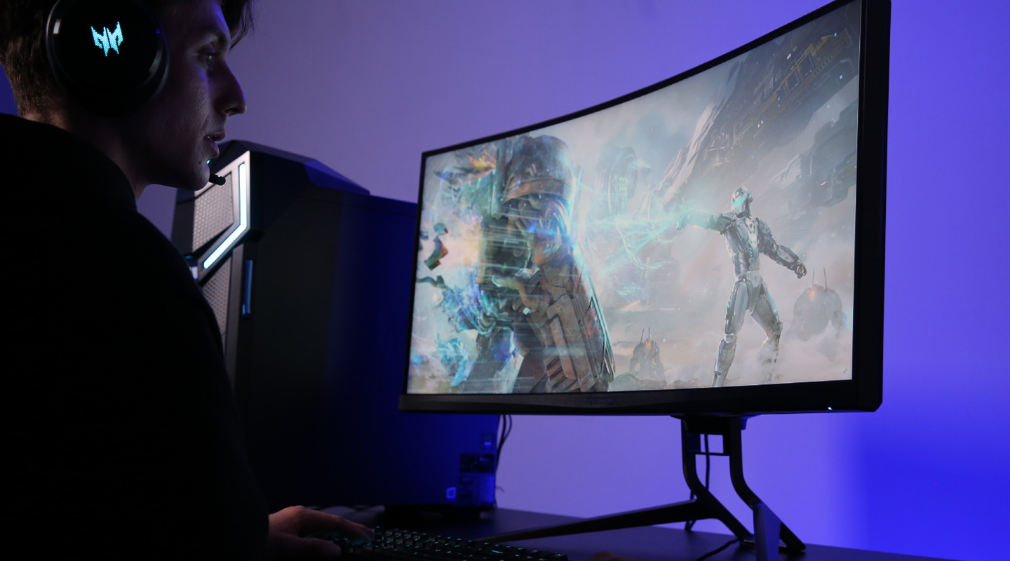 A man viewing a scifi video game screenshot on his Acer Predator X35 Monitor